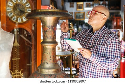 Focused elderly male collector of rare items making notes in notepad while visiting antique store