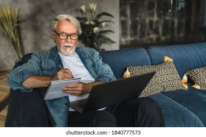 Konzentrierte ältere Menschen, die Noten in Notebooks schreiben und Webinar oder Online-Schulungen mit Laptop-Computer, moderne Senior-Männchen mit grauem Haar und Bart-Lernen online