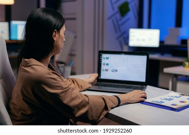 Focused entrepreneur checking business reports trying to finish a deadline. Businesswoman looking at statistics on laptpop screen sitting at her workplace doing overtime.