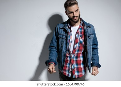 Focused fashion model looking away and walking while wearing jeans jacket on gray studio background