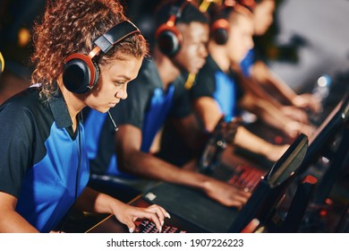 Focused female cybersport gamer wearing headphones participating in eSport tournament, sitting in a row with other team members and playing online video games