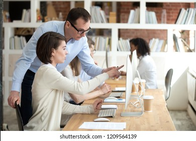 Focused female employee point at computer screen asking male teacher or trainer advice, woman worker show boss problem on pc monitor, manager or mentor help worker with report in coworking office