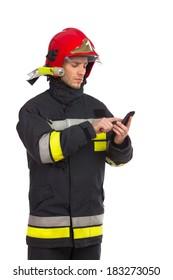 Focused fireman using smart phone. Three quarter length studio shot isolated on white.