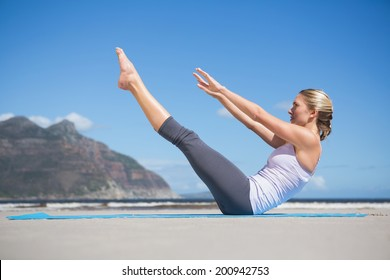 Focused fit blonde doing yoga on the beach on a sunny day