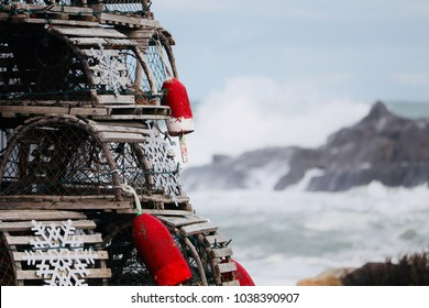 A focused foreground shot of stacked lobster traps with attached bouys with out of focus waves crashing on the rocks in the background.