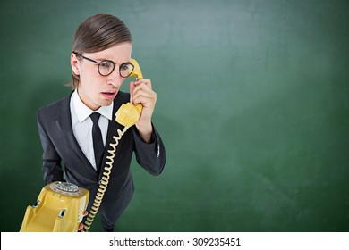 Focused geeky businessman on the phone against green chalkboard