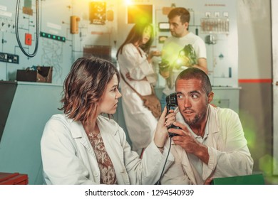 Focused girl and guy checking telephone set while trying to get out of escape room stylized as underground shelter