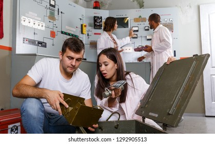 Focused girl and guy viewing contents of box while trying to get out of escape room stylized as underground shelter
