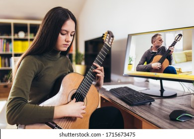 Focused girl playing acoustic guitar and watching online course on laptop while practicing at home. Online training, online classes.