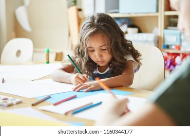 Focused girl with wavy hair sitting at table and drawing while attending art school