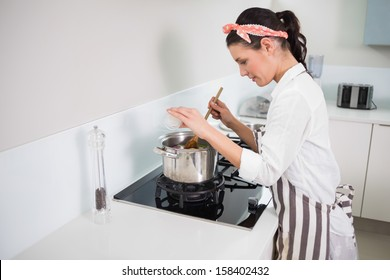 Focused gorgeous cook mixing vegetables in bright kitchen