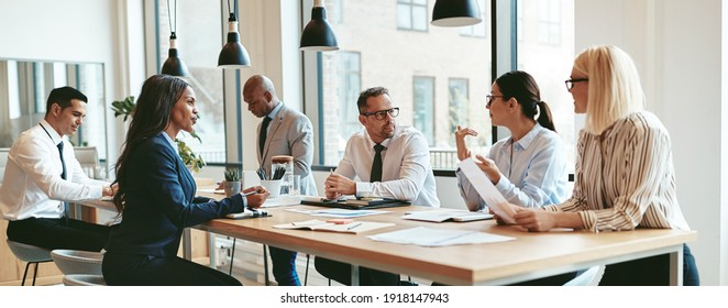 Focused group of diverse businesspeople discussing paperwork together during a meeting around a table in a modern office
