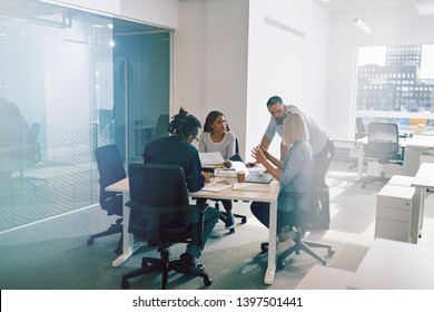 Focused group of diverse work colleagues having a meeting together around a table inside of a glass walled office