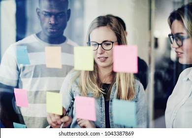 Focused group of diverse young businesspeople standing together in a modern office brainstorming with sticky notes on a glass wall