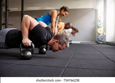 Focused group of fit people doing pushups with weights together on the floor during a health club class