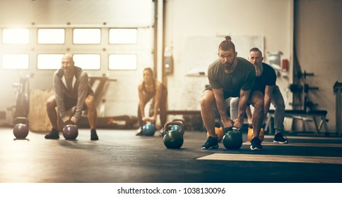 Focused group of fit people working out together with weights during an exercise class at a gym