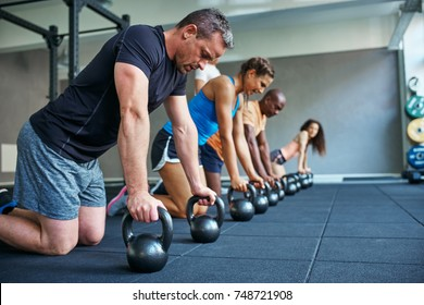 Focused group of fit people working out together on the floor with weights during a health club class