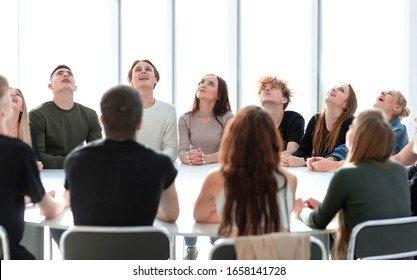 focused group of young people sitting at a round table