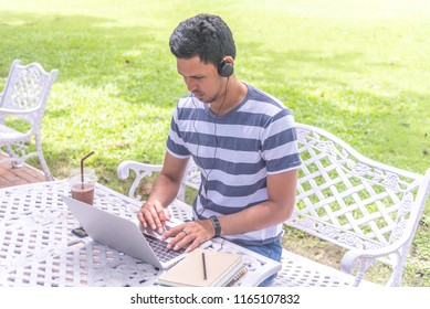 Focused handsome Asian man wearing headphones typing on laptop keyboard, serious student listening to audio business course, e-learning and online professional education concept