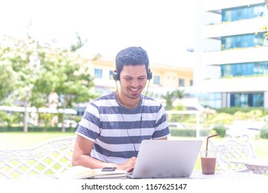 Focused handsome Asian man wearing headphones typing on laptop keyboard, smiling student listening to audio business course, e-learning and online professional education concept