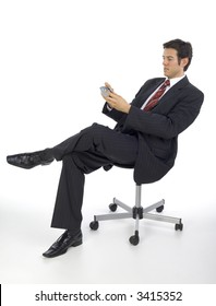 Focused, handsome businessman. Seating on chair with palmtop in hands. White background