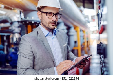 Focused handsome caucasian supervisor in suit and with helmet on head using tablet and looking at dashboard while standing in power plant.