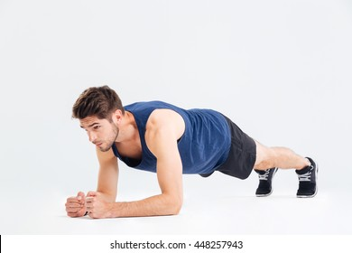 Focused handsome young sportsman doing plank core exercise over white background