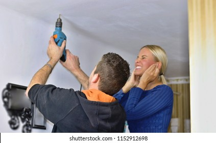 Focused handyman installing ceiling liners in the apartment interior with drill making too much noise. His assistant covering her ears. Handmade, manual work, teamwork and craft concept.