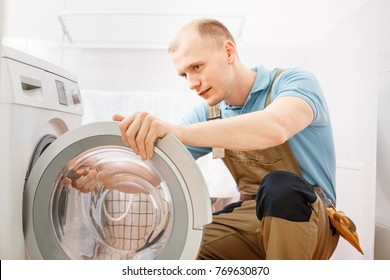 Focused handyman in overalls fixing a washing machine in the bathroom