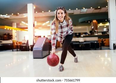 Focused happy woman enjoying bowling