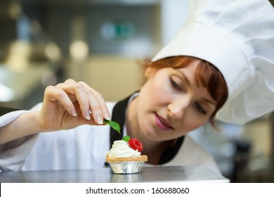 Focused head chef putting mint leaf on little cake in professional kitchen