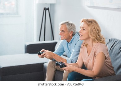 focused husband and wife playing video game with joysticks at home