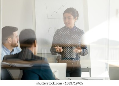 Focused indian woman stand making white board presentation for colleagues in conference room, concentrated millennial female speaker talk brainstorming with coworkers meeting at briefing