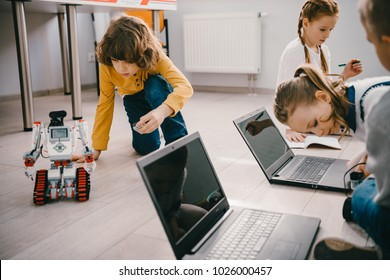 focused kids programming robots with computers while sitting on floor