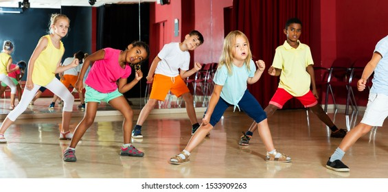 Focused kids studying modern style dance in class indoors