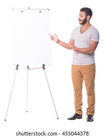 Focused latino man pointing on flip chart. He is making a presentation. Full length portrait isolated on white background.