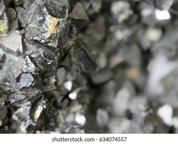 Focused left part of image showing mineral ore dark grey texture of a rocky lead zinc pattern crystalline structure