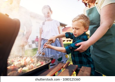 Focused little adorable toddler boy is carefully rotating meat and vegetables on a stick on a grill while being guided by his caring mother and supported by sister.