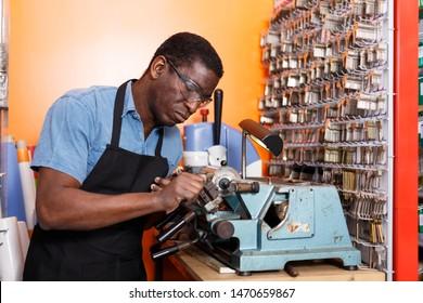 Focused locksmith working on key duplicating machine in workshop