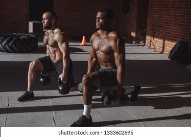 Focused male african and caucasian athletes showing determination and endurance exercising legs and back musculs during body core crossfit workout