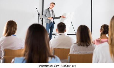 Focused male coach giving presentation for adult audience in lecture hall