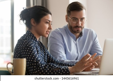 Focused male intern listening to serious indian business woman mentor teacher explaining online strategy looking at laptop computer teach trainee training new worker learning new skill at workplace