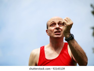 A Focused male runner with the blue sky behind him, with a really intense look on his face.
