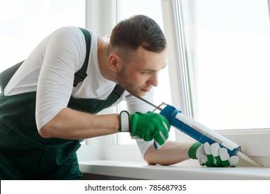 Focused man is applying sealant using a caulking gun. Call a repairman to fix your house. Handyman service.