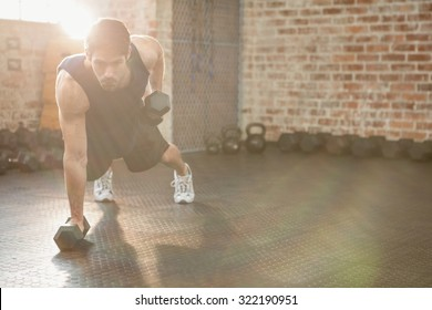 Focused man lifting dumbbell at the gym