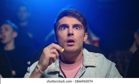 Focused man looking interesting film in dark hall. Portrait of surprised guy eating popcorn in movie theater. Closeup worried male person spending evening in cinema.