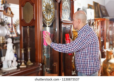 Focused  man rubbing surface of vintage items with cloth in store of antique goods