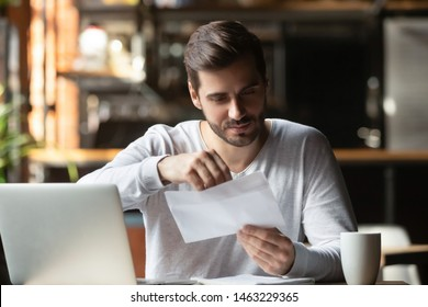 Focused man sitting in cafe working on laptop drinking coffee open post envelop get message from college, concentrated male student receive reply from university unwrap letter correspondence