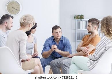 Focused man talking to people in white room during AA meeting