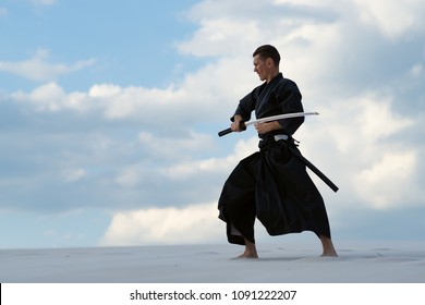 Focused man, in traditional clothes, is practicing Japanese martial art - iaido in the desert with a Japanese sword - a katana during sunset on the background of evening sky. Side view.